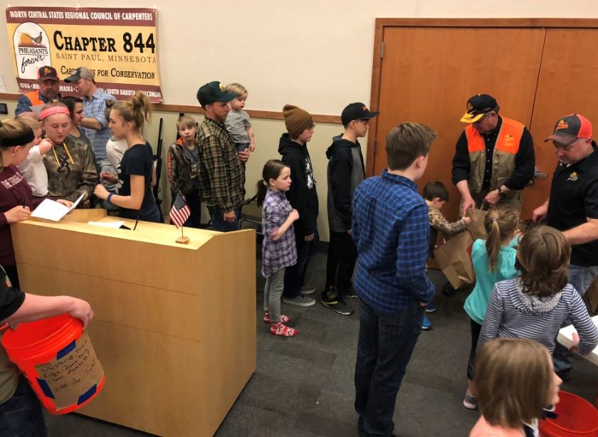 Youth lined up for a grocery grab bag of hunting and outdoor related goodies.